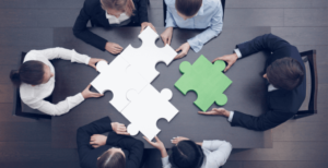Businesspeople-around-table-putting-together-large-puzzle-team-building-680x350